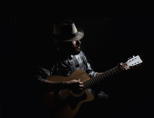 Young hipster guitarist play on the acoustic guitar .